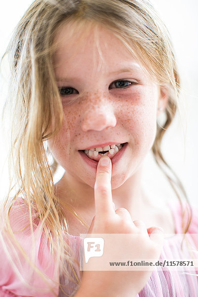 Portrait of girl pointing at missing teeth