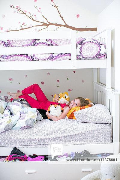 Porträt eines auf einem Etagenbett liegenden Mädchens mit Plüschtieren
