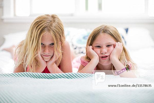 Porträt eines Mädchens und einer Schwester  die im Bett Gesichter ziehen