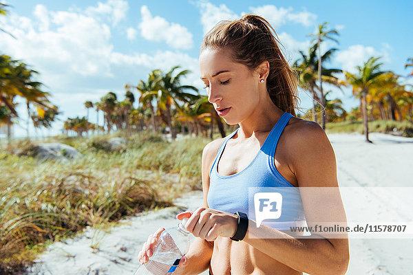 Junge weibliche Läuferin sitzt mit Flaschenwasser am Strand