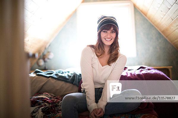Porträt einer jungen Frau  drinnen  mit Strickmütze  lächelnd
