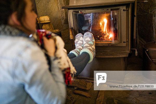 Junge Frau wärmt die Füße vor dem Feuer