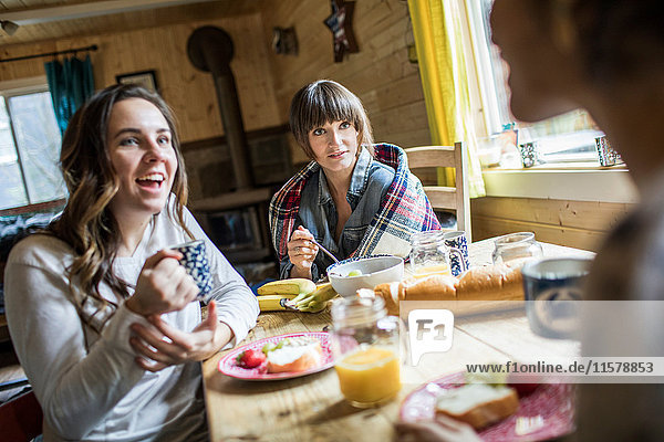 Drei Freunde sitzen am Tisch und frühstücken.