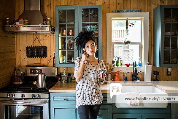 Porträt einer jungen Frau  die in der Küche steht und ein heißes Getränk hält.