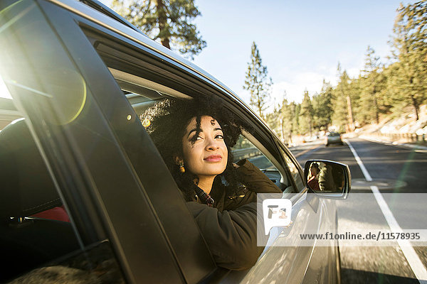 Young woman looking out of window of moving car