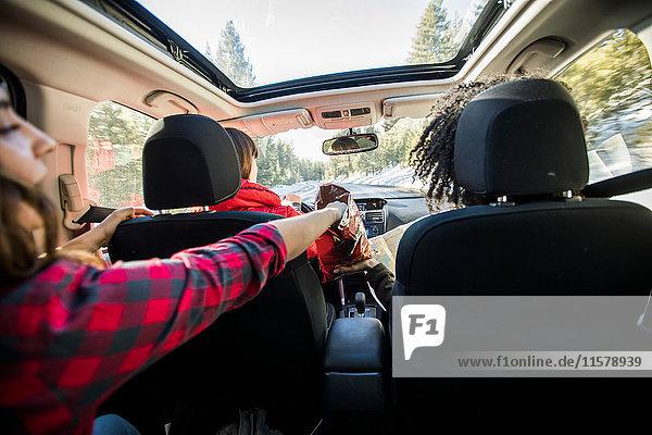 Drei Freunde im fahrenden Auto  zwei Freunde teilen sich Chips