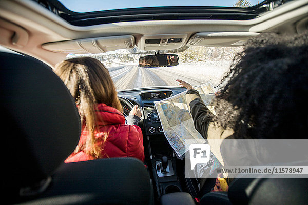 Woman driving car  friend in passenger seat looking at map