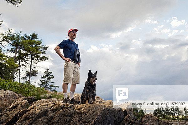 Älterer Mann und Hund schauen auf die Küste von Maine  USA