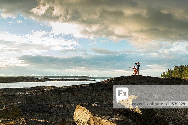 Fernblick eines älteren Mannes und seines Sohnes durch ein Fernglas an der Küste von Maine  USA