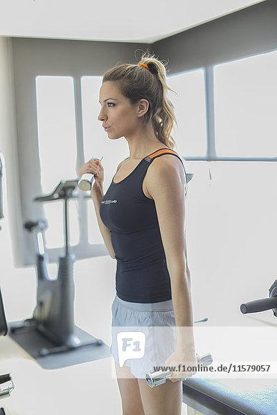 Hübsche Frau beim Gewichtheben im Fitnessstudio