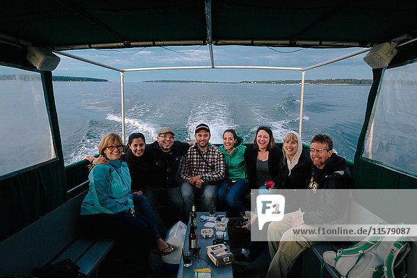 Porträt einer erwachsenen Familie  die in einem Boot auf See nahe der Küste von Maine  USA  sitzt