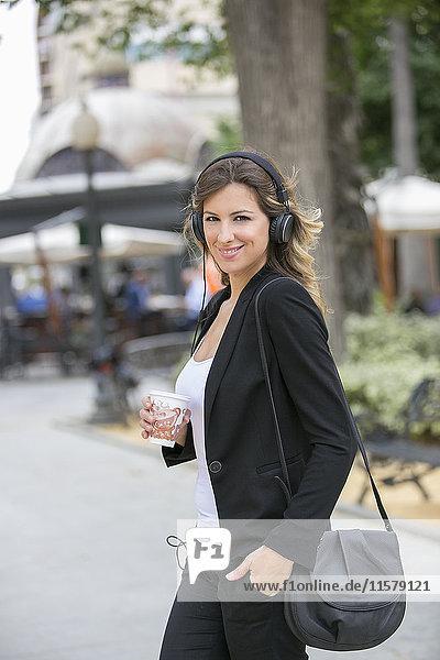 Hübsche Geschäftsfrau mit Kopfhörern  die in der Innenstadt spazieren geht.