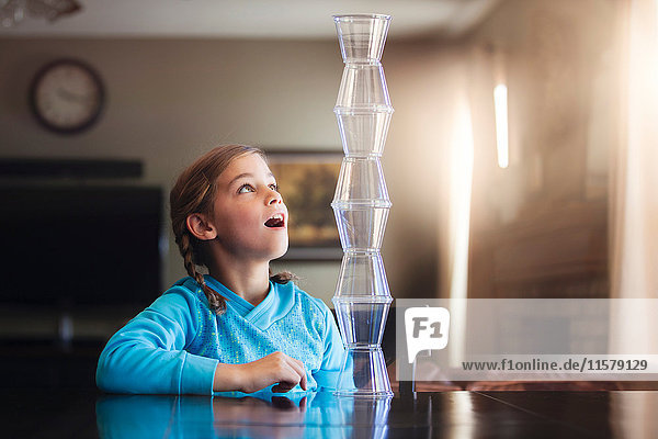 Girl looking in awe at balanced plastic cups