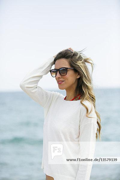 Hübsche blonde Frau mit Sonnenbrille am Strand
