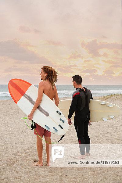 Männlicher Rettungsschwimmer und Surfer  der vom Strand auf das Meer schaut