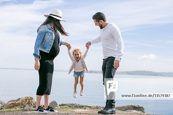 Schwangeres reifes Paar schwingt Tochter an der Küste