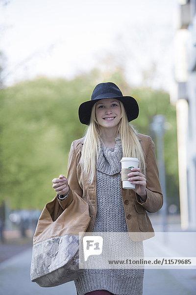 Hübsche blonde Frau mit Hut und Kaffee  die vor der Kamera lächelt und im Stadtzentrum spazieren geht.