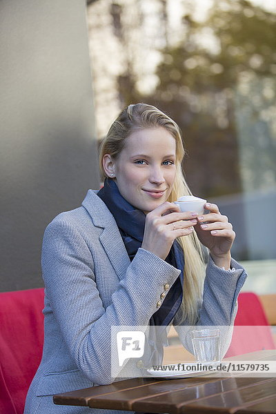 Hübsche blonde Frau genießt eine Tasse Kaffee in einem Cafe und lächelt in die Kamera.