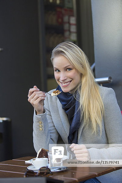 Pretty blonde woman enjoying a cake and coffee in city center smiling at camera
