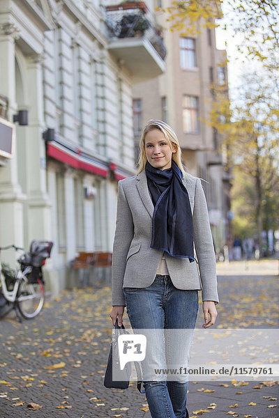 Hübsche elegante Frau mit Handtasche im Stadtzentrum