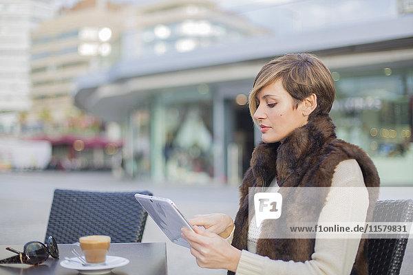 Frau mit Tablette in einem Cafe im Freien