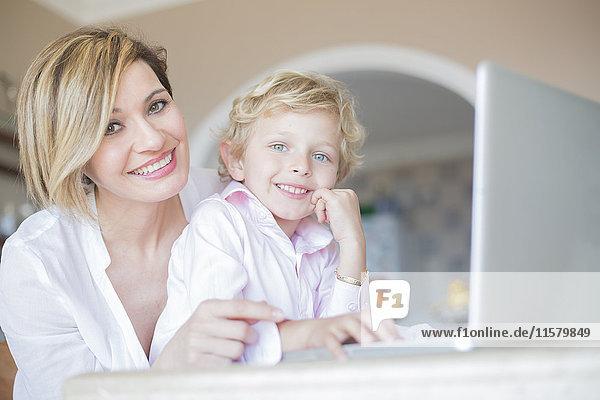 Mutter und Sohn mit Laptop zu Hause lächelnd vor der Kamera