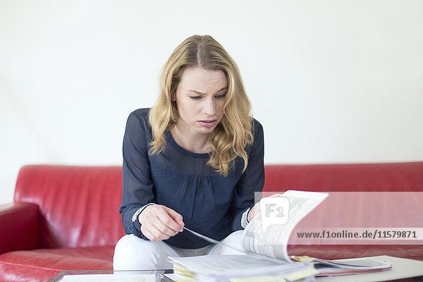 Blonde Frau mit Rechnungen überhäuft