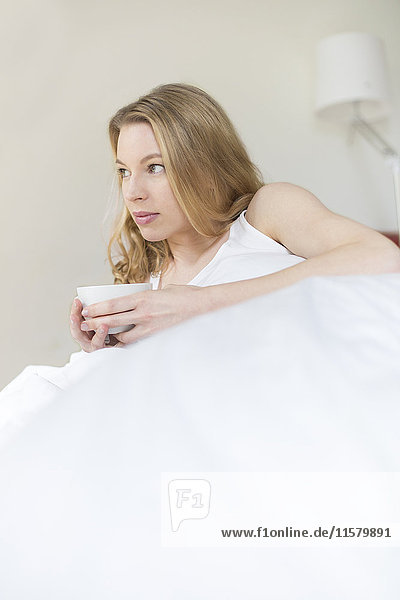 Hübsche  nachdenkliche Frau mit einer Tasse im Bett.