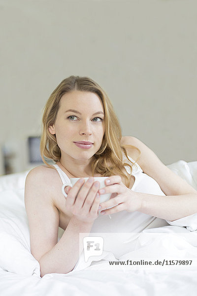 Hübsche  nachdenkliche Frau genießt einen Tee im Bett.