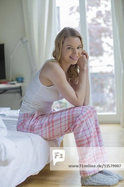 Hübsche blonde Frau sitzt auf dem Bett und lächelt vor der Kamera.