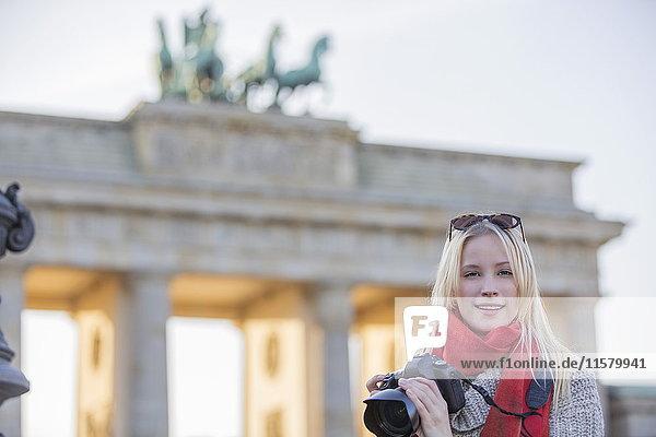 Hübsche blonde Frau fotografiert vor dem Brandenburger Tor in Berlin und schaut in die Kamera.