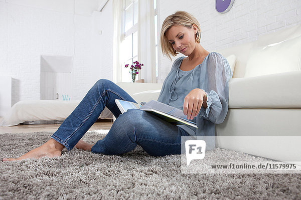 Mid adult woman sitting on rug reading book