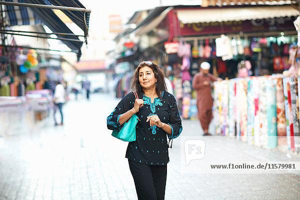 Mature female tourist strolling in market at Sharjah  United Arab Emirates