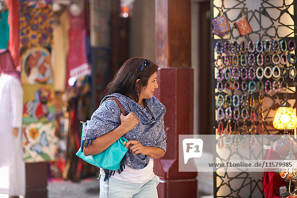 Mature female tourist strolling and looking at market stall  Sharjah  United Arab Emirates