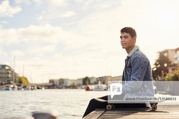 Junger Mann sitzt am Fluss  Skateboard neben ihm  Bristol  UK