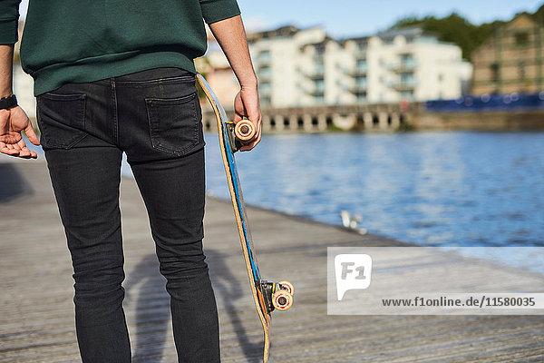 Junger Mann geht am Fluss entlang  hält Skateboard  Rückansicht  Mittelteil  Bristol  UK