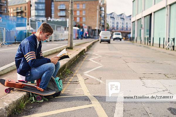 Junger Mann sitzt auf dem Bordstein  liest ein Buch  neben ihm ein Skateboard  Bristol  UK