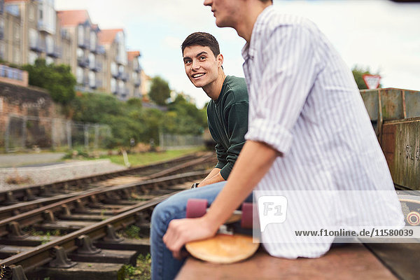 Zwei junge Männer sitzen an einem Zuggleis  Bristol  UK