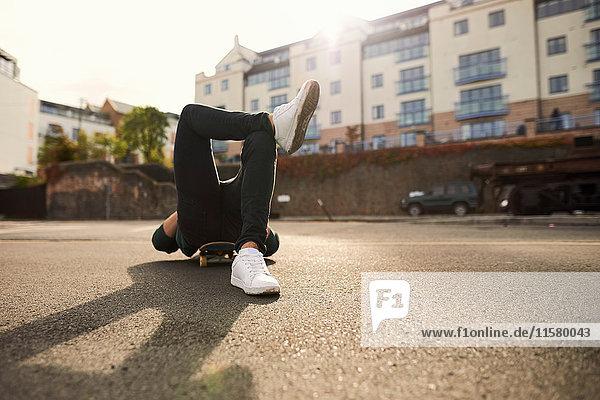 Junger Mann auf Skateboard liegend  entspannend  Bristol  UK