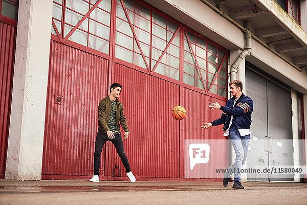 Zwei junge Männer spielen Basketball in einem städtischen Gebiet  Bristol  UK