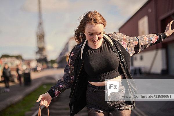 Junge Frau balanciert auf Zuggleisen  Bristol  UK