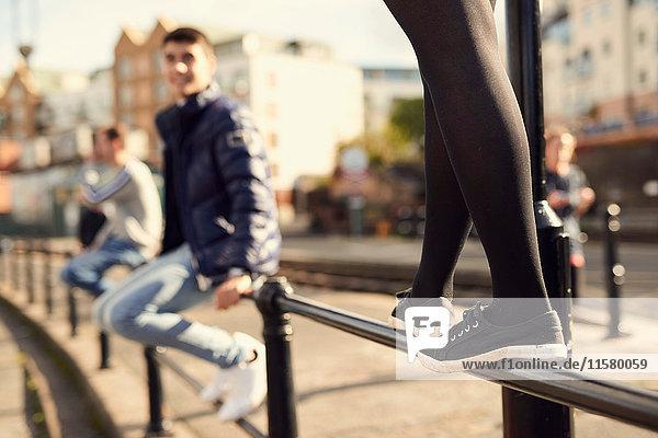 Junger Mann sitzt auf einem Geländer  ein junges Mädchen geht neben ihm am Geländer entlang  Bristol  UK