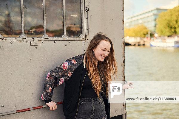 Junge Frau beim Herumalbern am Fluss  Bristol  UK