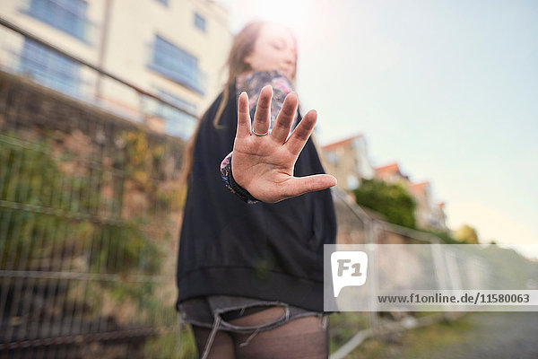 Junge Frau geht im Freien  hält Hand an die Kamera  Rückansicht  Bristol  UK