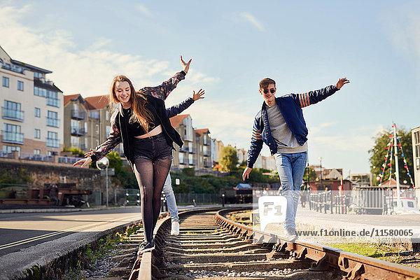 Drei Freunde balancieren auf Zuggleisen  Bristol  UK