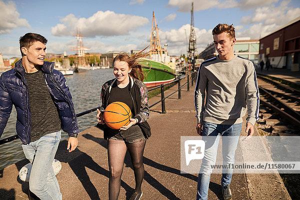 Drei Freunde gehen am Fluss entlang  junge Frau trägt Basketball  Bristol  UK