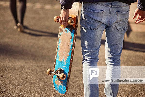 Junger Mann geht im Freien  Skateboard tragend  Rückansicht  niedriger Abschnitt  Bristol  UK