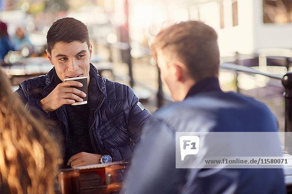 Drei Freunde sitzen im Freien und trinken Kaffee  Bristol  UK