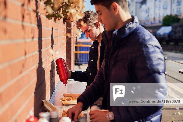 Zwei junge Männer am Imbissstand  die Ketchup auf das Essen schütten  Bristol  UK