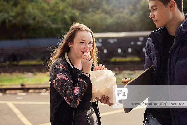 Junger Mann teilt eine Tüte Chips mit einer jungen Frau  Skateboard unter dem Arm eines jungen Mannes  Bristol  UK